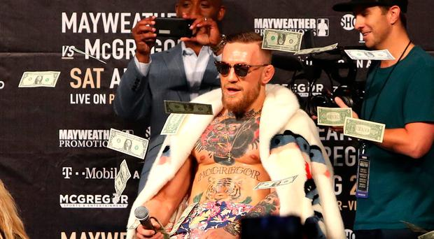 NEW YORK, NY - JULY 13: Conor McGregor looks on as money rains down during the Floyd Mayweather Jr. v Conor McGregor World Press Tour event at Barclays Center on July 13, 2017 in the Brooklyn borough of New York City. (Photo by Mike Lawrie/Getty Images)