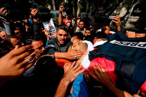 Mourners and journalists carry the body of Yasser Murtaja, during his funeral in Gaza City yesterday. Photo: Mahmud Hams/Getty