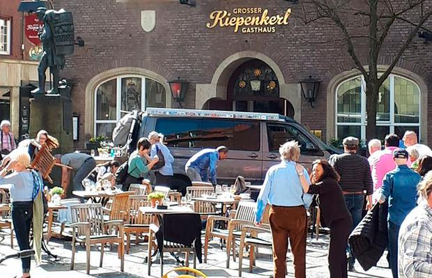 People stay in front of a restaurant in Muenster, Germany, Saturday, April 7, 2018 after a vehicle crashed into a crowd (Stephan R./dpa via AP)