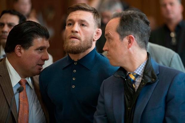 Conor McGregor stands with his lawyer Jim Walden, right, and John Arlia during his arraignment in Brooklyn federal court. Photo: AP