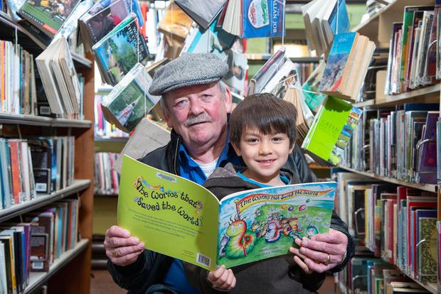 James O'Geady and grandson Liam O'Burre, from Ballinlough, catch up on some reading in Cork's famous English Market. Photo: Gerard McCarthy
