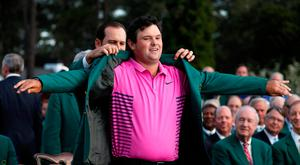 Sergio Garcia of Spain (rear), last year's Masters' champion, helps put the Green Jacket on 2018 Masters winner Patrick Reed following final round play of the 2018 Masters golf tournament at the Augusta National Golf Club in Augusta, Georgia, U.S. April 8, 2018. REUTERS/Jonathan Ernst TPX IMAGES OF THE DAY