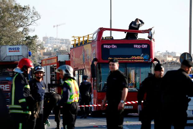 A forensics investigator stands on an open top, double-decker sightseeing bus after it crashed into some low-lying tree branches, in Zurrieq, Malta April 9, 2018. REUTERS/Darrin Zammit Lupi