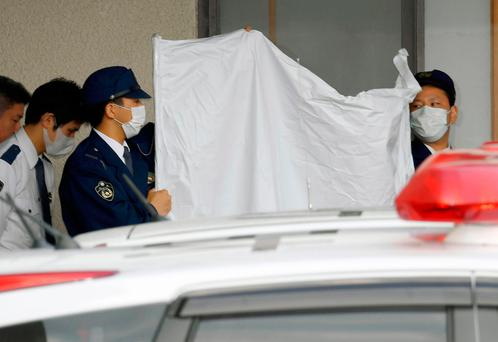 Police officers hide the face of arrested Japanese Yoshitane Yamasaki with a sheet while escorting him to a police vehicle to leave for Prosecutor's Office for further investigation, in Sanda City, western Japan, Monday, April 9, 2018. (Yohei Nishimura/Kyodo News via AP)