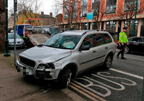 A garda at the damaged Volvo car on Waterloo Road in Dublin, where it crashed before the occupants fled. Photo: Collins