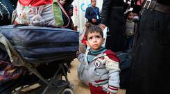 A young boy keeps an hand on the family luggage as Syrian families gather at a camp for displaced people from Douma yesterday. Photo: Nazeer al-Khatib/Getty