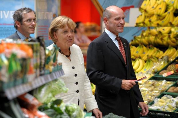 Karl-Erivan Haub (R) of the retailer group Tengelmann and German Chancellor Angela Merkel of the Christian Democratic Union (CDU) visit a Tengelmann supermarket during an election campaign rally in the western town of Muelheim, Germany, August 20, 2009. REUTERS/Federico Gambarini/Pool/File Photo