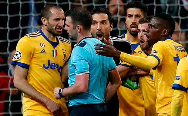 Juventus' Gianluigi Buffon and Giorgio Chiellini appeal to referee Michael Oliver after he awarded a penalty to Real Madrid REUTERS/Stringer