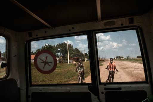 Streetviews of Bentiu town. Two kids drive on a bicycle behind the MSF Car. Bentiu is the administrative, political and commercial center of former Unity State in South Sudan. Violence over the years has left the town in ruins, with signs of the war everywhere.