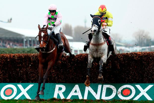 Politologue ridden by Sam Twiston-Davies (right) jumps a fence before winning the JLT Melling Chase ahead of Min