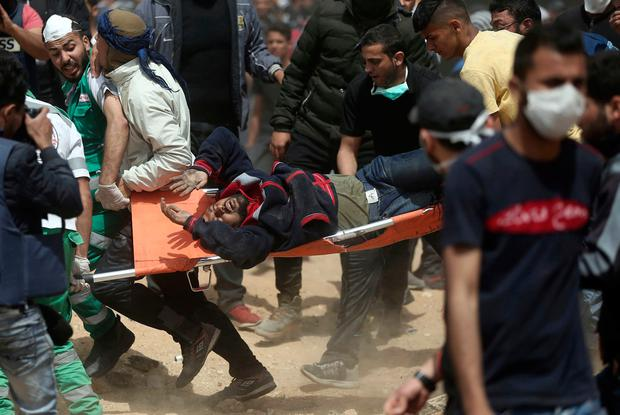 Palestinian protesters evacuate a wounded man during a protest at the Gaza Strip's border with Israel, yesterday. Photo: Khalil Hamra/AP