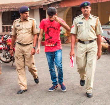 Vikhat Bhagat, accused of raping and murdering Danielle McLaughlin, is escorted by a police officer in India