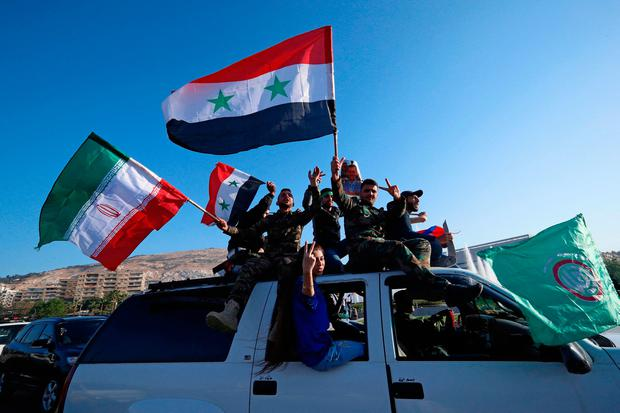 Syrian government supporters wave Syrian, Iranian and Russian flags as they chant slogans against U.S. President Trump during demonstrations following a wave of U.S., British and French military strikes in Damascus, Syria. (AP Photo/Hassan Ammar)