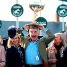 GRAND DAY: Michael O'Leary celebrates with his wife (left) and trainer Gordon Elliott (right in navy jacket) after winning the Randox Health Grand National Handicap Chase with Tiger Roll at Aintree Racecourse. Picture: PA