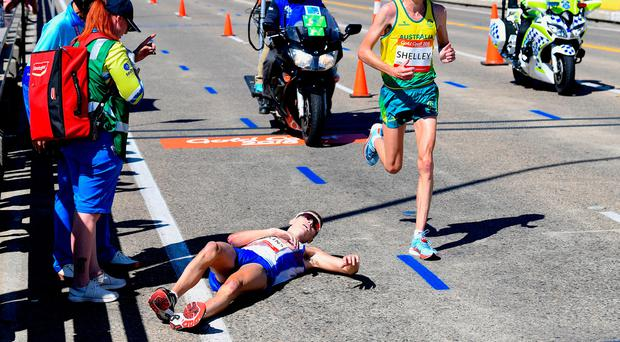 Scotland's Callum Hawkins lies on the ground as Australia's Michael Shelley runs past during the Men's Marathon Final at the Commonwealth Games on the Gold Coast in Australia, April 15, 2018. AAP/Tracey Nearmy/via REUTERS