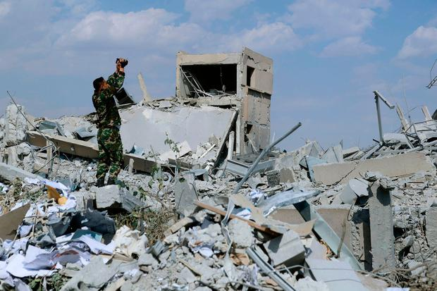 A soldier films the damage of the Syrian Scientific Research Centre in Barzeh, near Damascus after it was attacked by US, British and French military strikes. (AP Photo/Hassan Ammar)