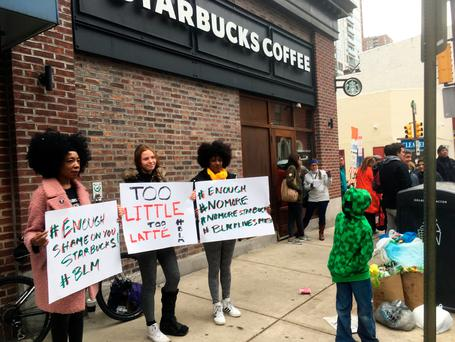 Protesters gather outside a Starbucks in Philadelphia, Sunday, April 15, 2018, where two black men were arrested Thursday after Starbucks employees called police to say the men were trespassing. (AP Photo/Ron Todt)