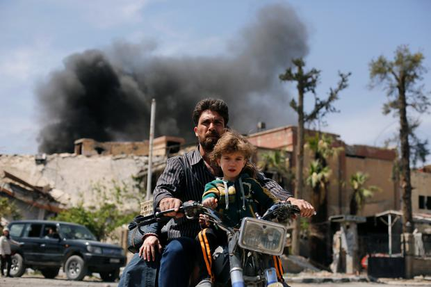 A man and a boy ride a motorbike in the city of Douma, near Damascus, where the Syrian regime launched a chemical attack last weekend. Photo: Reuters/Omar Sanadiki
