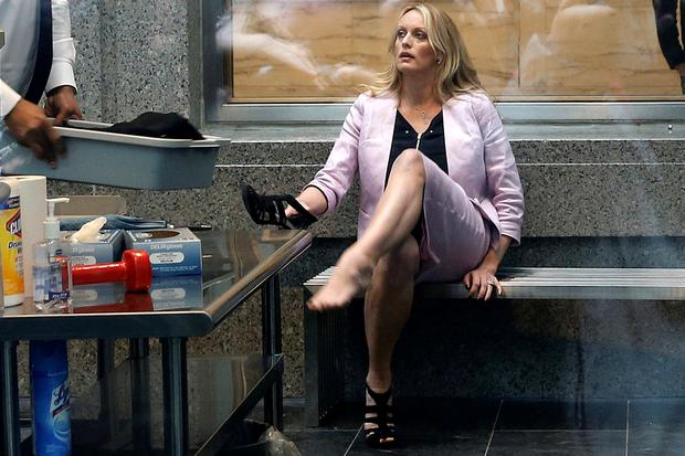 Stormy Daniels puts her shoe back on after passing though a security screening. Photo: Reuters