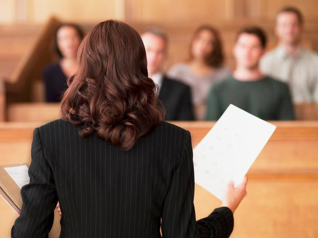 Lawyer holding document and speaking to jury in courtroom. Stock image.