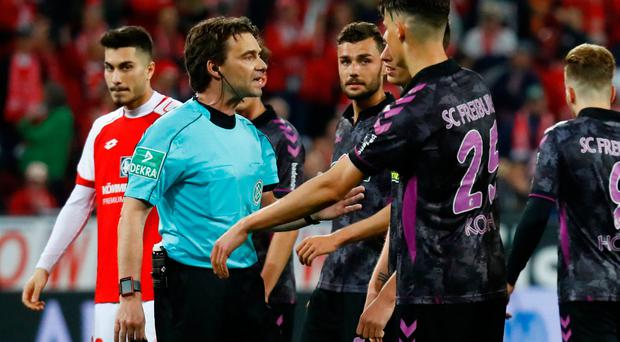 SC Freiburg's Robin Koch speaks with referee Guido Winkmann after a penalty is awarded to Mainz