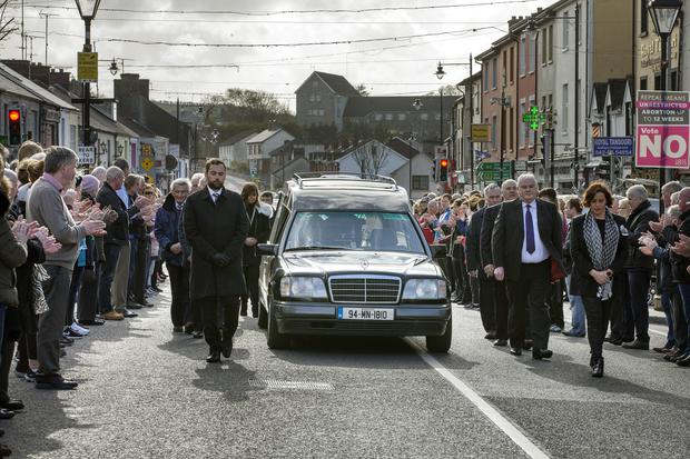 Former band members accompany the coffin of Big Tom McBride as it is applauded through the centre of Castleblaney, Co. Monaghan. Photo: Tony Gavin.