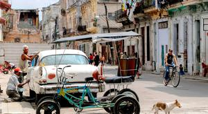 People go on with their daily lives in the sun-drenched backstreets of Havana yesterday. Photo: Getty Images