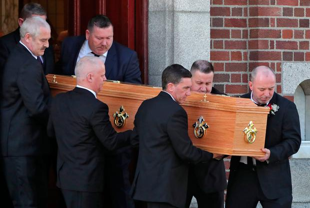 Family members carry Brian Hamilton's coffin out of church