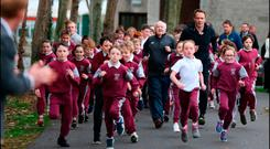 Frank Greally, Athletics Ireland's ambassador for the Daily Mile, and teacher Patrick Lowery, with children from St Brigid's National School, Castleknock, last week. Photo: David Conachyof