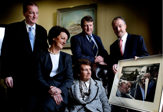 The former Taoiseach's wife looks at a photograph of her husband alongside children Ciaran, Eimear, Conor and Sean at the formal announcement of the handing over of his private papers to DCU