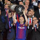 Barcelona's Spanish midfielder Andres Iniesta (C) holds the trophy