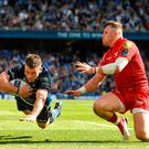 Leinster's Fergus McFadden scores his side's third try despite the tackle of Steff Evans of Scarlets. Photo: Ramsey Cardy