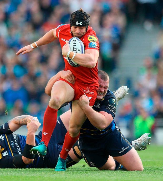Leinster's Jack McGrath tackles Scarlets' Leigh Halfpenny. Photo: Lorraine O'Sullivan/PA Wire