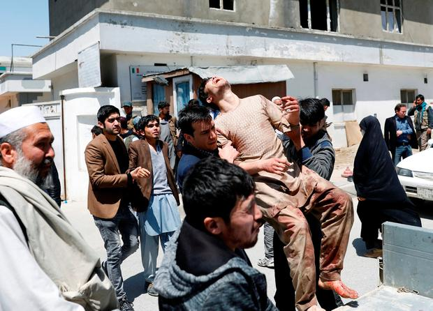 Relatives of the victims carry an injured man outside a hospital after a suicide attack in Kabul, Afghanistan April 22, 2018.REUTERS/Mohammad Ismail