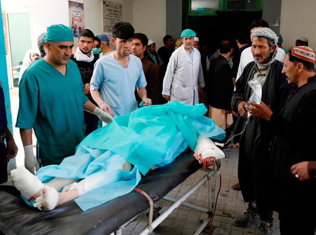 Men carry a victim to an ambulance at a hospital after a suicide attack in Kabul, Afghanistan April 22, 2018.REUTERS/Mohammad Ismail