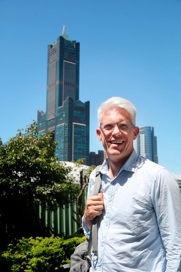 David enjoys the sunshine, with 85 Sky Tower Hotel in Kaohsiung in the background