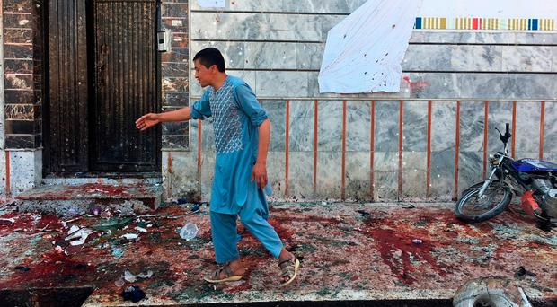 Isil suicide bomber kills 57 as Afghans queue for voting cards