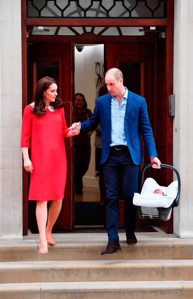 The Duke of Cambridge holds the hand of his wife, the Duchess of Cambridge, as he carries their newborn son from the Lindo Wing at St Mary's Hospital in Paddington, London