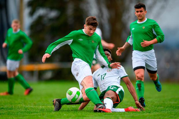 Eric O'Halloran of Irish Defence Forces and Carlton Ubaezuonu of the Irish College & Universities challenge for possession. Photo: Harry Murphy/Sportsfile