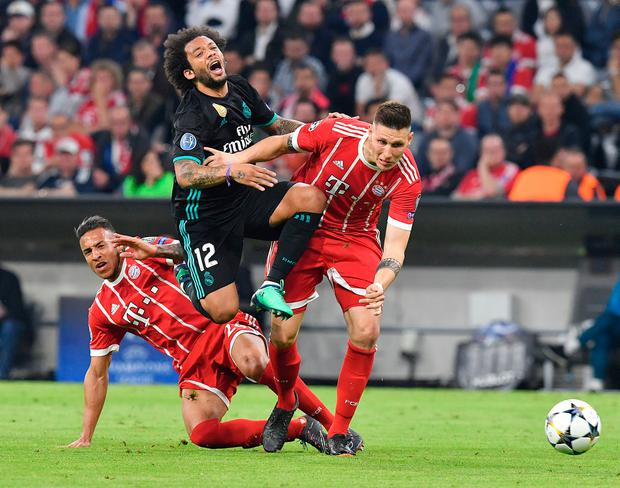 Bayern's Corentin Tolisso, left, Real Madrid's Marcelo, center, and Bayern's Niklas Suele challenge for the ball. Photo: Kerstin Joensson/AP Photo