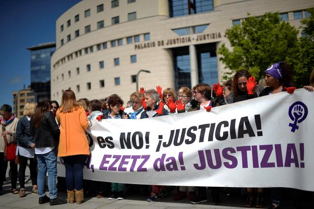 Protesters gather outside the High Court of Navarra behind a banner reading