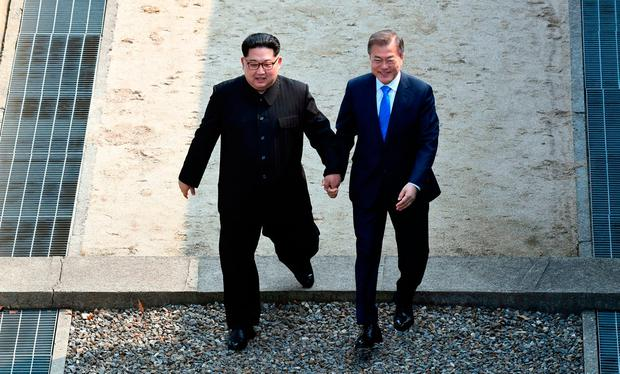 Kim Jong-un, left, and Moon Jae-in cross the border line together. Photo: AP