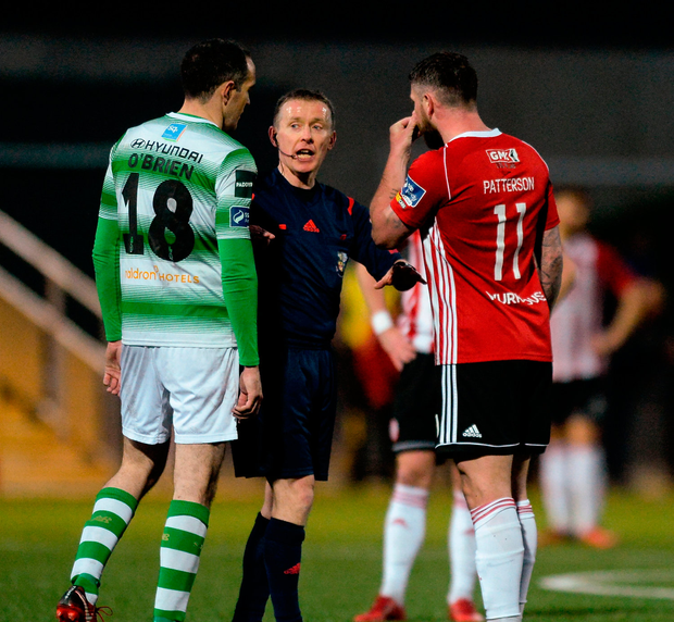 Referee Derek Tomney in discussion with Joey O'Brien of Shamrock Rovers and Rory Patterson of Derry City