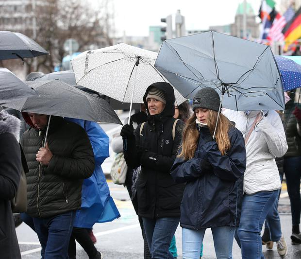 Tourists shelter from the rain on O'Connell Street in Dublin City. Picture: Damien Eagers
