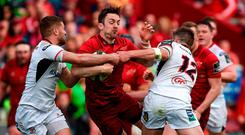 Munster's Darren Sweetnam is tackled by Ulster duo Johnny McPhillips and Stuart McCloskey in Thomond Park yesterday. Photo: Diarmuid Greene/Sportsfile