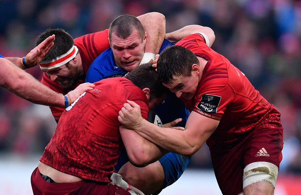 CJ Stander, supported by Munster teammates Billy Holland, left, and Tommy O'Donnell, right, is tackled by Jack McGrath of Leinster