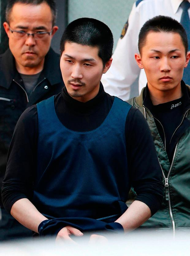 Japanese fugitive Tatsuma Hirao is escorted as he leaves a police department in Hiroshima after he was arrested on April 30, 2018.AFP PHOTO / JIJI PRESS / JIJI PRESS / Japan OUTJIJI PRESS/AFP/Getty Images