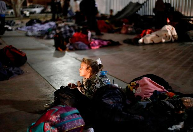 A girl and other members of a caravan of migrants from Central America get ready to spend the night near the San Ysidro checkpoint after a small group of fellow migrants entered the United States border and customs facility, where they are expected to apply for asylum, in Tijuana, Mexico April 29, 2018. REUTERS/Edgard Garrido