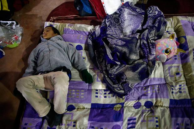 A member of a caravan of migrants from Central America sleeps near the San Ysidro checkpoint after a small group of fellow migrants entered the United States border and customs facility, where they are expected to apply for asylum, in Tijuana, Mexico April 29, 2018. REUTERS/Edgard Garrido