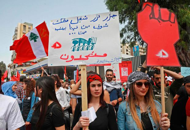 Supporters of the Lebanese Communist Party brandish a national flag and banners during a rally celebrating the International Labour Day in the Lebanese capital Beirut. Photo: AFP/Getty Images